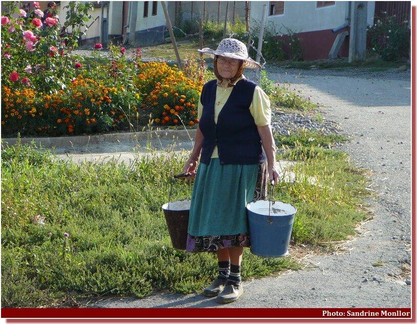 Vieille dame portant des seaux d'eau potable en Roumanie