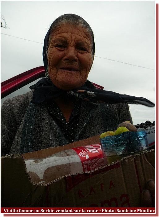 Vieille femme en serbie vendant au bord de la route