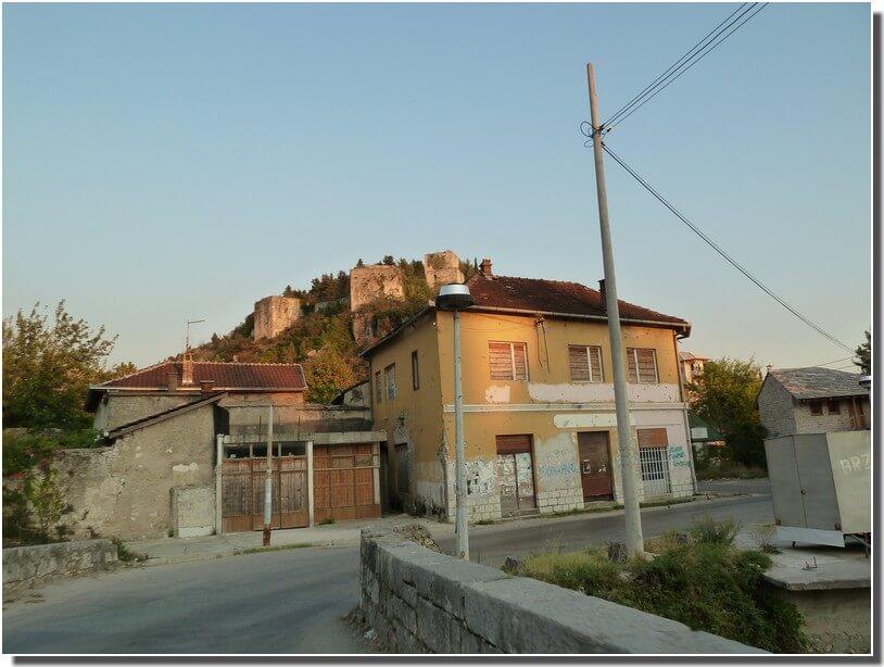 Route traversant Stolac vue d'une maison et du chateau en ruines