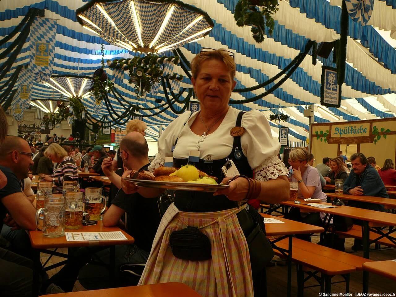 Serveuse en habits bavarois apportant un plat typique de viandes et knodels à la fête de la bière de Munich