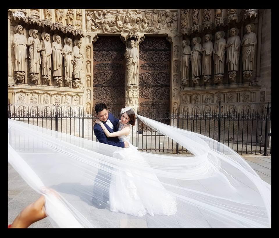 Séance photos de mariage d'un couple chinois assistante tenant le voile devant Notre Dame de Paris