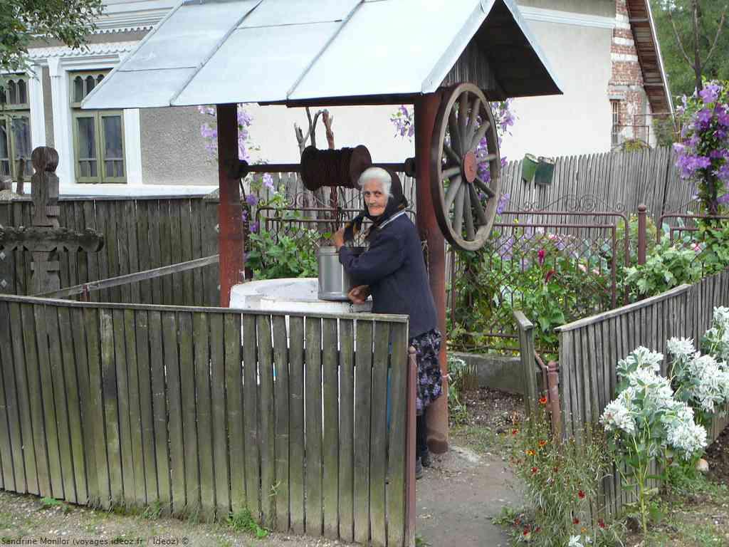 Vieille femme récupérant de l'eau au puits