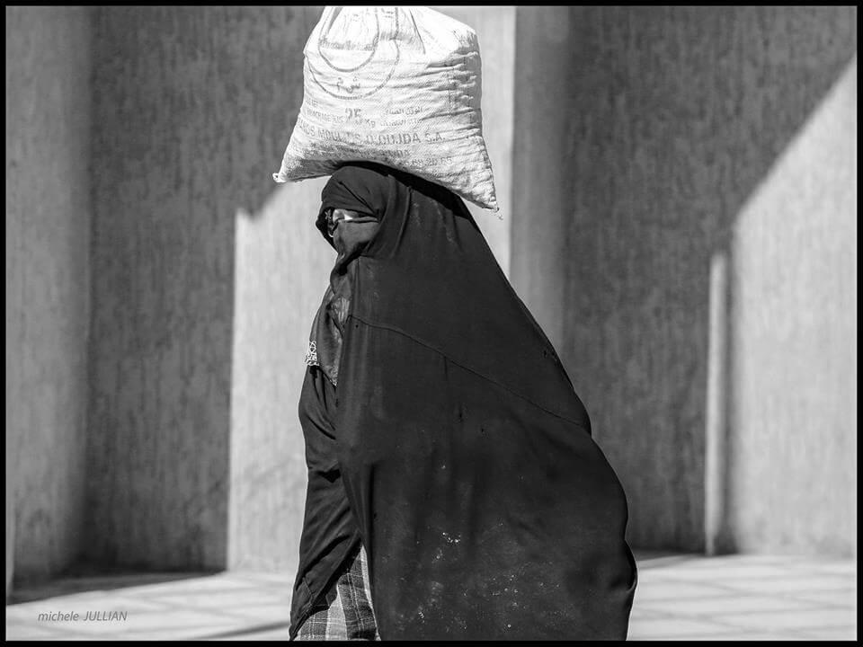 Rissani femme marocaine portant sur sa tête une lourde charge