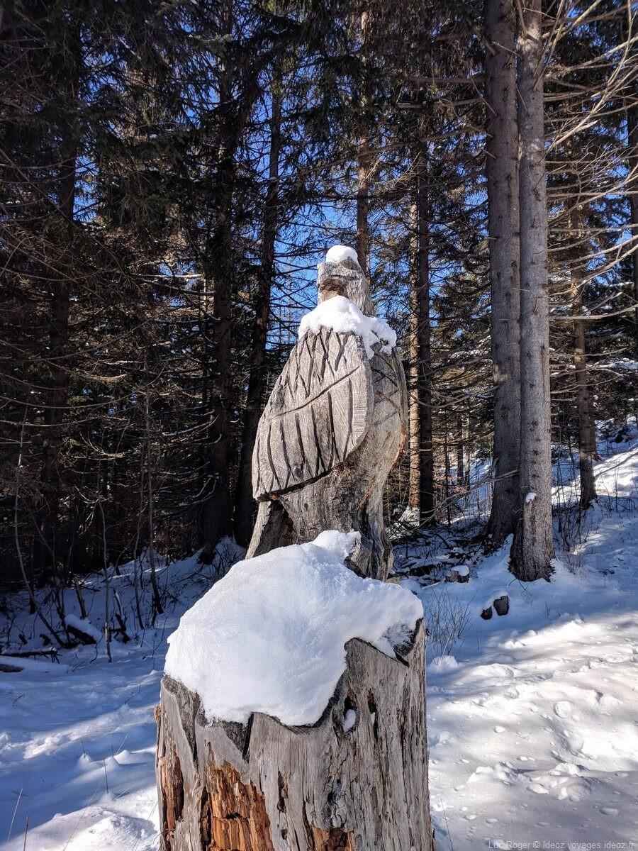 sculpture d'un aigle en bois sous la neige