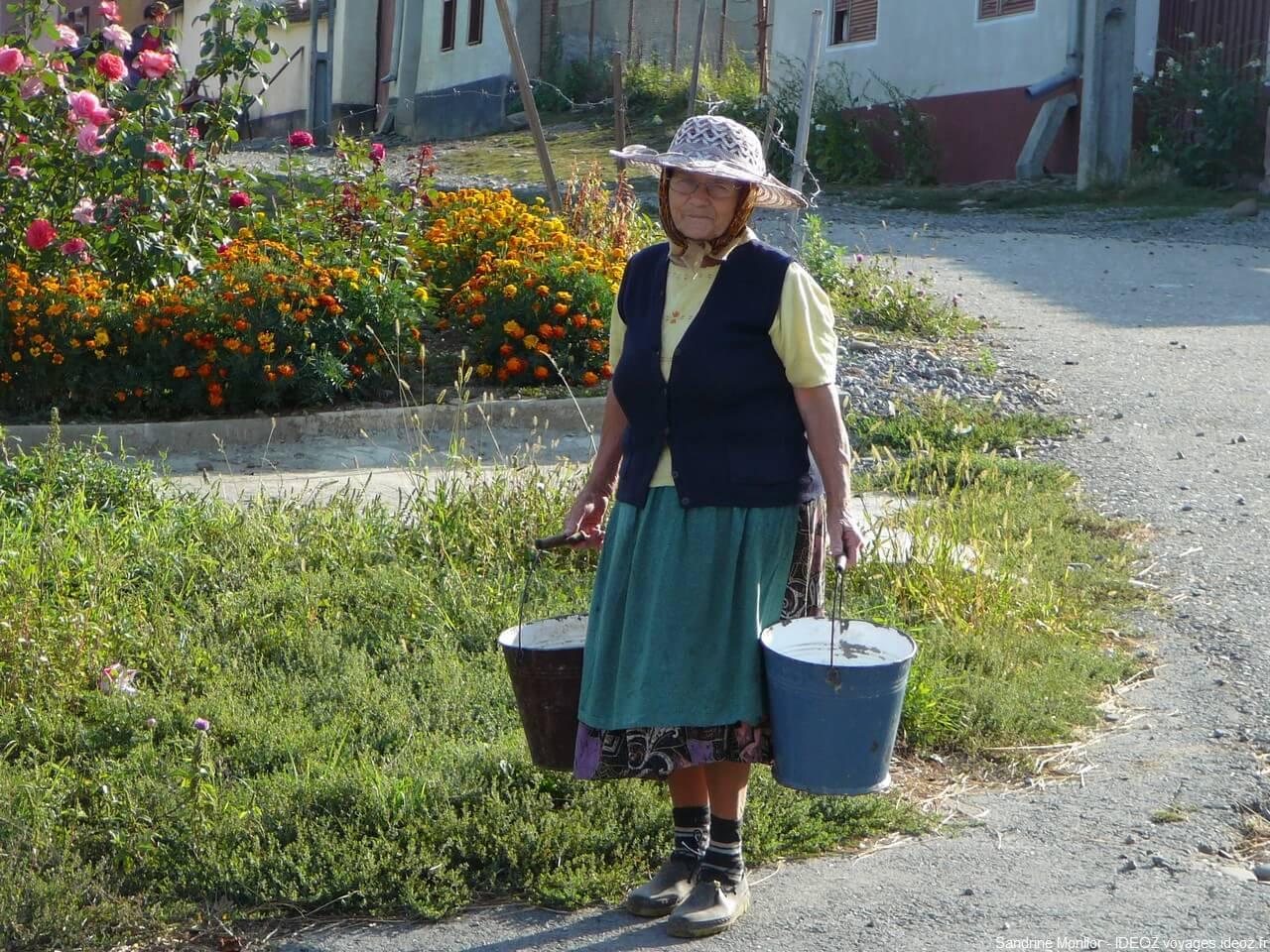 Vieille femme en Roumanie portant des seaux d'eau pour arroser son jardin