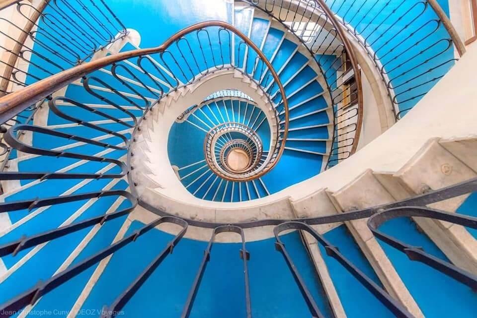 escalier aux marches bleues en colimaçon dans un immeuble Bauhaus Budapest