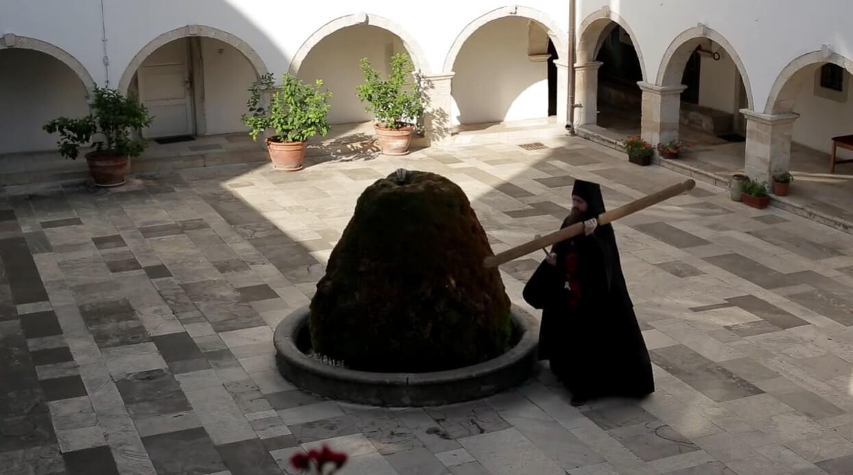 moine portant un simandre dans la cour du monastère krka