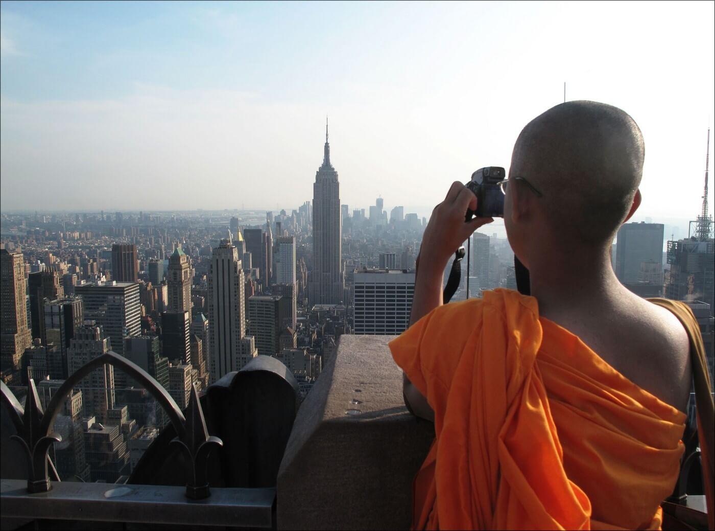 moine bouddhiste prenant de la hauteur pour photographier la ville de new york