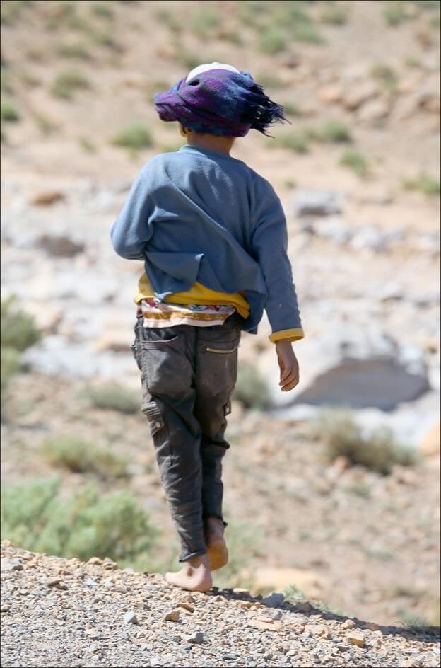 enfant nomade au maroc marchant sans chaussure ruban dans le vent