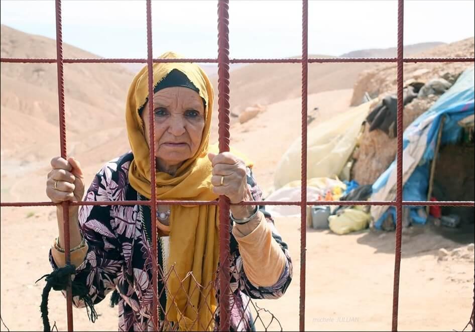 femme berbère derrière des grilles dans un bivouac au maroc