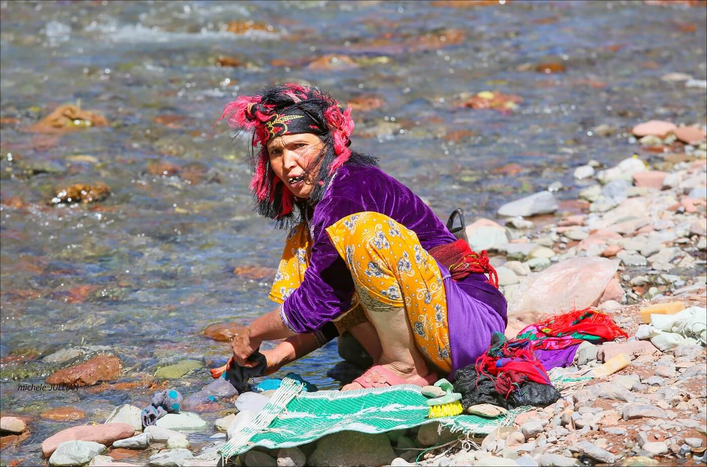 femme berbère lavant son linge dans une rivière au maroc