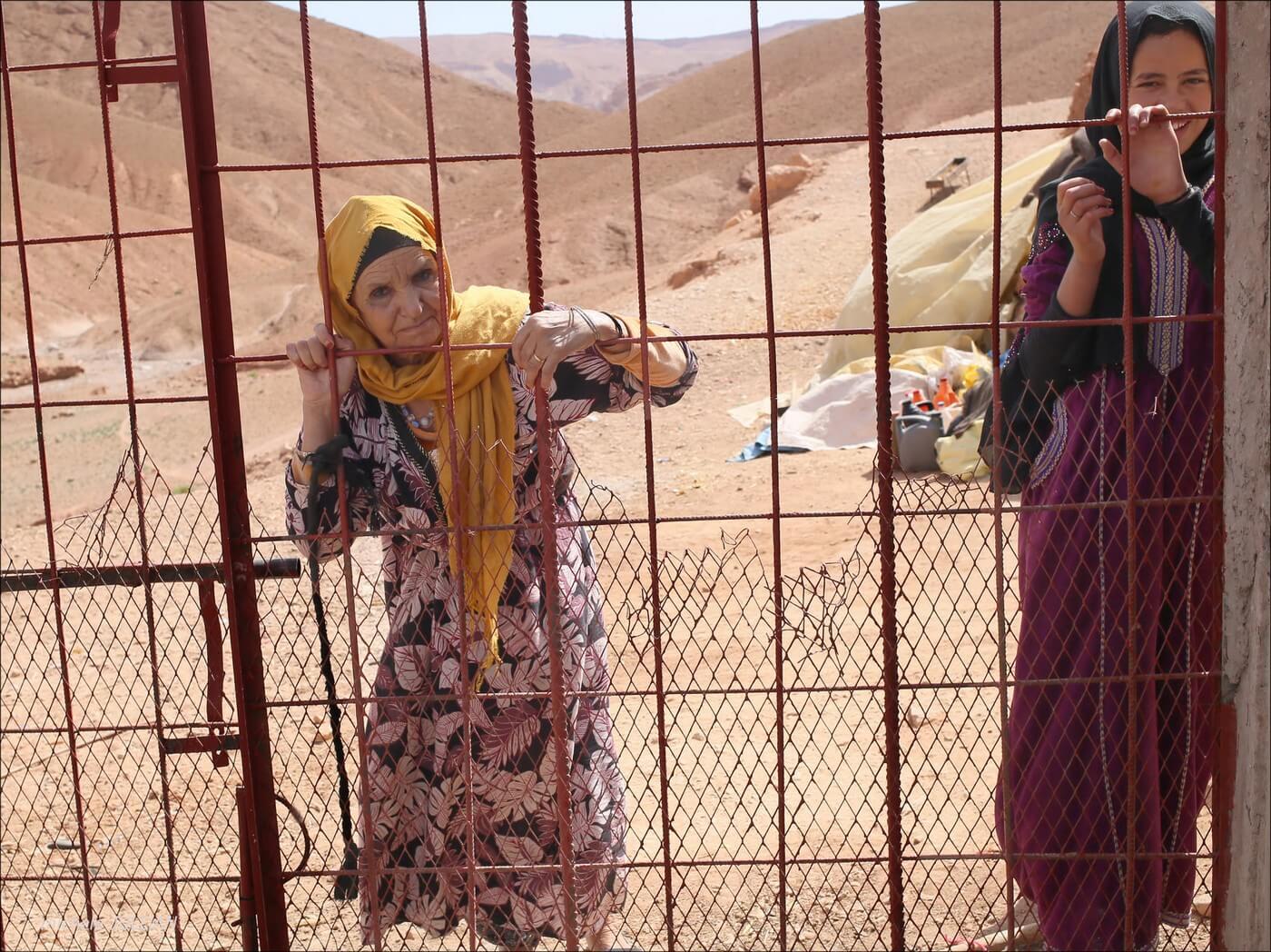 femmes berbères derrières des grilles dans un bivouac au maroc