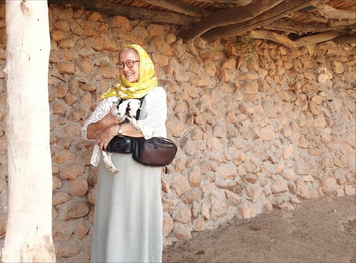 michele jullian portant un agneau dans un village berbère au maroc