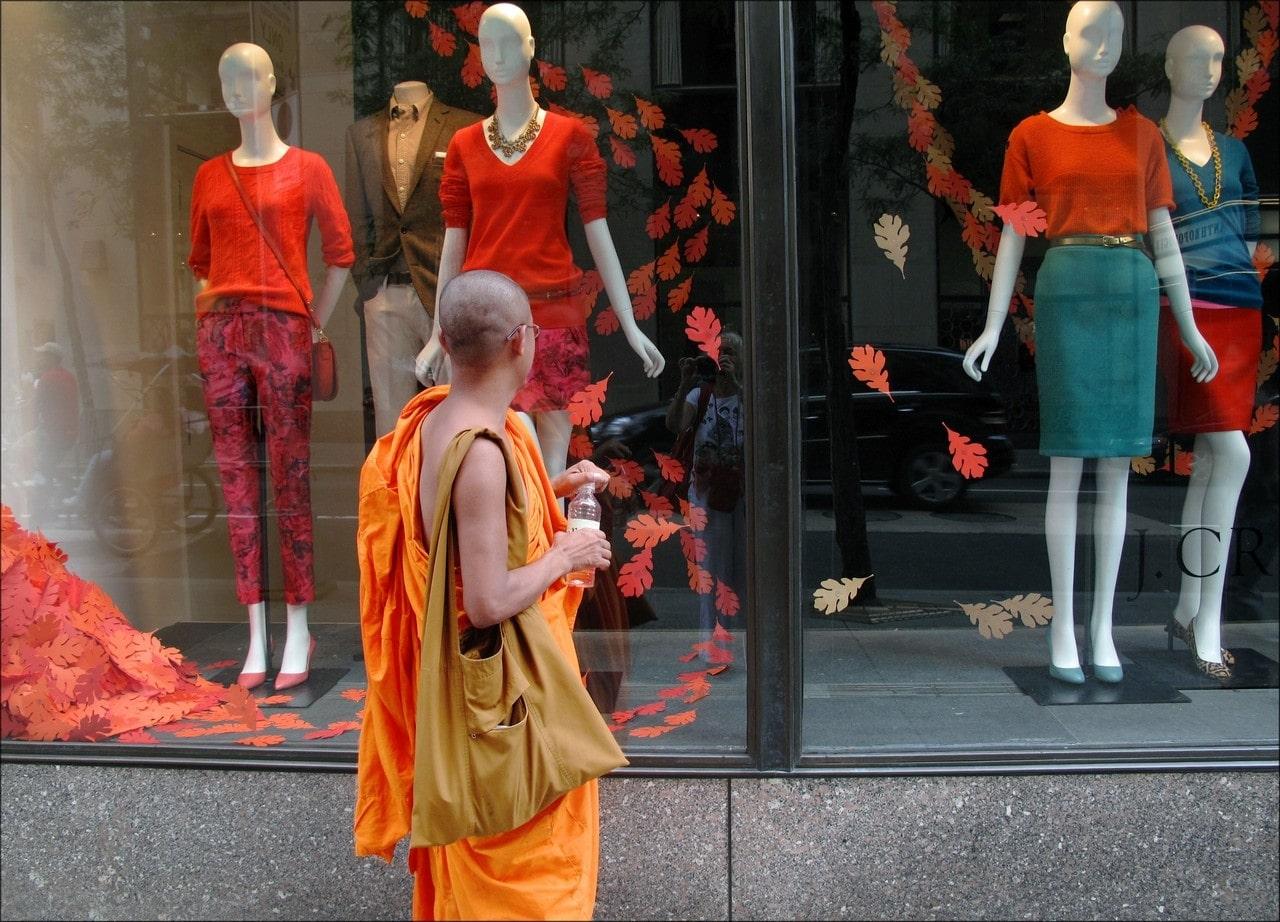 moine bouddhiste devant une vitrine de mode à new york
