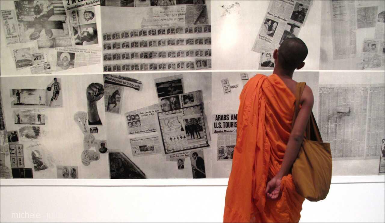 moine bouddhiste en train de découvrir une exposition de coupures de presse à new york