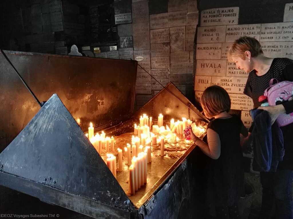 kamenita vrata fillette allumant un cierge près des ex voto