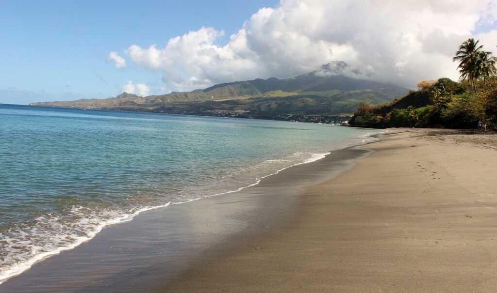 plage de sable fin en martinique avec la montagne pelée